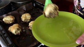 Uma mulher põe o prato terminado sobre uma placa Bifes triturados da carne com batatas, ovos e queijo vídeos de arquivo