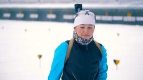 Uma mulher põe sobre uma arma dos esportes O atleta do Biathlon toma uma arma e põe-na sobre uma parte traseira filme