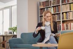 uma mulher, uma pessoa 40 anos velha, guardando o copo de café, lendo o compartimento, na biblioteca, livrarias, livrarias, senta Fotografia de Stock Royalty Free
