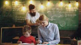 Uma mulher pinta com um menino em uma sala de aula da escola no fundo de um homem que lê um livro O menino tira com professores