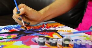 Uma mulher pinta uma imagem da pintura preta video estoque