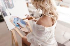 Uma mulher pinta uma imagem Fotos de Stock Royalty Free