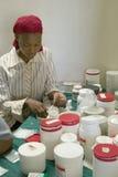Uma mulher prepara comprimidos do SIDA no programa de reabilitação de Pepo La Tumaini Jangwani, da comunidade de HIV/AIDS, no orf foto de stock