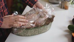 Uma mulher prepara uma galinha para a repreensão no forno A mulher na cozinha que prepara o jantar vídeos de arquivo