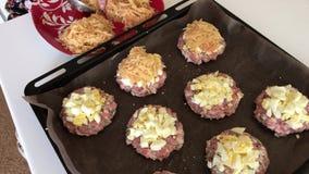 Uma mulher prepara o alimento Bifes triturados da carne com batatas, ovos e queijo Cozinhando etapas e ingredientes vídeos de arquivo