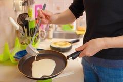 Uma mulher prepara panquecas, derrama a massa em uma frigideira quente imagem de stock