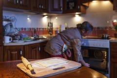 Uma mulher prepara tortas, aquece o forno Imagens de Stock