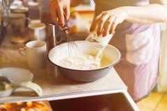 Uma mulher prepara um prato da farinha Foto de Stock