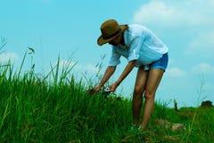 Uma mulher que anda em torno do campo do arroz e do fundo bonito do céu azul, olha feliz e relaxa Fotografia de Stock