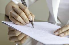 Uma mulher que assina um contrato Imagens de Stock