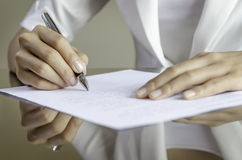 Uma mulher que assina um contrato Fotografia de Stock Royalty Free