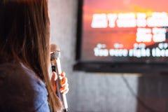 Uma mulher que canta na barra do karaoke que guarda um microfone na frente da tela da tevê com poemas líricos foto de stock