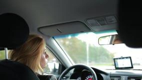 Uma mulher que conduz um carro passeios atentos da menina em torno da cidade vídeos de arquivo