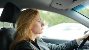 Uma mulher que conduz um carro passeios atentos da menina em torno da cidade video estoque
