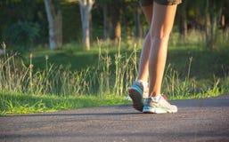 Uma mulher que corre na manhã para movimentar-se, exercitar e healt imagens de stock