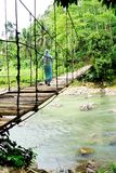 Uma mulher que cruza uma ponte de suspensão Imagem de Stock