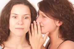 Uma mulher que diz o segredo a outra Foto de Stock Royalty Free
