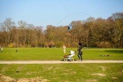 Uma mulher que empurra um carrinho de criança olha um homem voar um papagaio imagens de stock