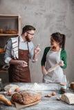 Uma mulher que escuta as instruções de um homem sobre o pão do cozimento fotografia de stock