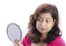 Uma mulher que faz a composição com seu espelho Fotografia de Stock Royalty Free