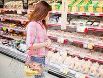 Uma mulher que faz compras na mercearia com cesto de compras imagem de stock royalty free