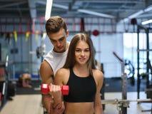 Uma mulher que faz exercícios com pesos em um fundo do gym Um instrutor pessoal que ajuda um cliente em um clube de aptidão foto de stock