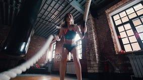Uma mulher que faz o crossfit no gym Treinando suas mãos com as cordas que batem no assoalho video estoque
