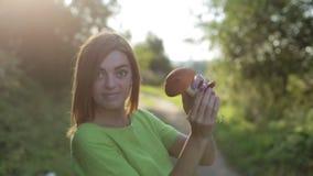 Uma mulher que giram ao redor e mostras um cogumelo, que encontrasse na floresta filme