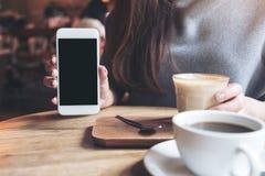 Uma mulher que guarda e que mostra o telefone celular branco com a tela preta vazia do desktop com os copos de café na tabela de  Imagem de Stock