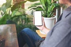 Uma mulher que guarda e que usa o telefone celular preto com a tela desktop vazia e fundo verde da natureza fotos de stock