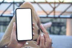 Uma mulher que guarda o telefone celular preto com a tela desktop branca da placa ao estabelecer na sala de visitas com sentiment imagem de stock