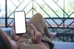 Uma mulher que guarda o telefone celular preto com a tela desktop branca da placa ao estabelecer na sala de visitas com sentiment imagens de stock royalty free