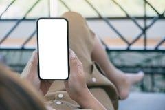 Uma mulher que guarda o telefone celular preto com a tela desktop branca da placa ao estabelecer na sala de visitas com sentiment fotografia de stock royalty free