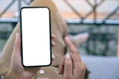 Uma mulher que guarda o telefone celular preto com a tela desktop branca da placa ao estabelecer na sala de visitas com sentiment fotografia de stock