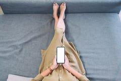 Uma mulher que guarda o telefone celular preto com a tela desktop branca da placa ao estabelecer na sala de visitas com sentiment foto de stock royalty free