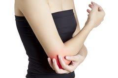 Uma mulher que guarda seu cotovelo na dor, com o vermelho destacado na área da dor em um fundo branco Imagens de Stock