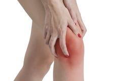 Uma mulher que guarda seu joelho na dor, com o vermelho destacado na área da dor em um fundo branco Fotografia de Stock Royalty Free