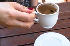 Uma mulher que guarda um copo do café turco foto de stock