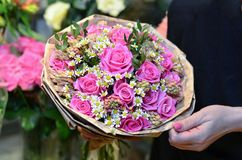 Uma mulher que guarda um ramalhete das rosas envolvidas no papel foto de stock