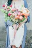 Uma mulher que guarda um ramalhete decorativo das flores em suas mãos fotografia de stock royalty free