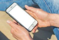 Uma mulher que guarda um telefone celular branco com uma tela vazia imagens de stock