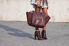 Uma mulher que guarda uma bolsa do desenhista e que veste montantes imagem de stock royalty free