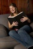 Uma mulher que lê um livro grande Fotos de Stock Royalty Free