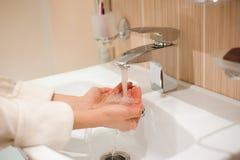 Uma mulher que lava suas mãos no dissipador imagens de stock