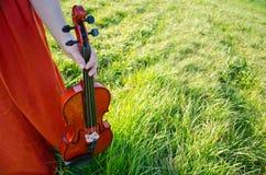 Uma mulher que mantem um violino na natureza horizontal Imagens de Stock Royalty Free