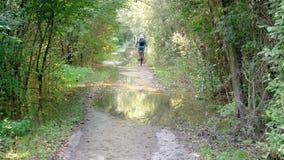 Uma mulher que monta sua bicicleta em uma estrada de terra com as poças perto dos arbustos video estoque