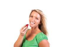 Uma mulher que morde uma morango deliciosa suculenta Foto de Stock