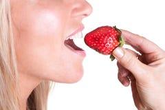 Uma mulher que morde uma morango deliciosa suculenta Fotos de Stock