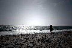 Uma mulher que olha o horizonte infinito em um dia ensolarado brilhante em um litoral Fotografia de Stock