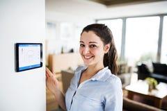 Uma mulher que olha a tabuleta com a tela home esperta imagem de stock royalty free